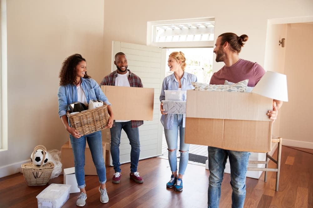 friends,help,couple,to,carry,boxes,into,new,home,on
