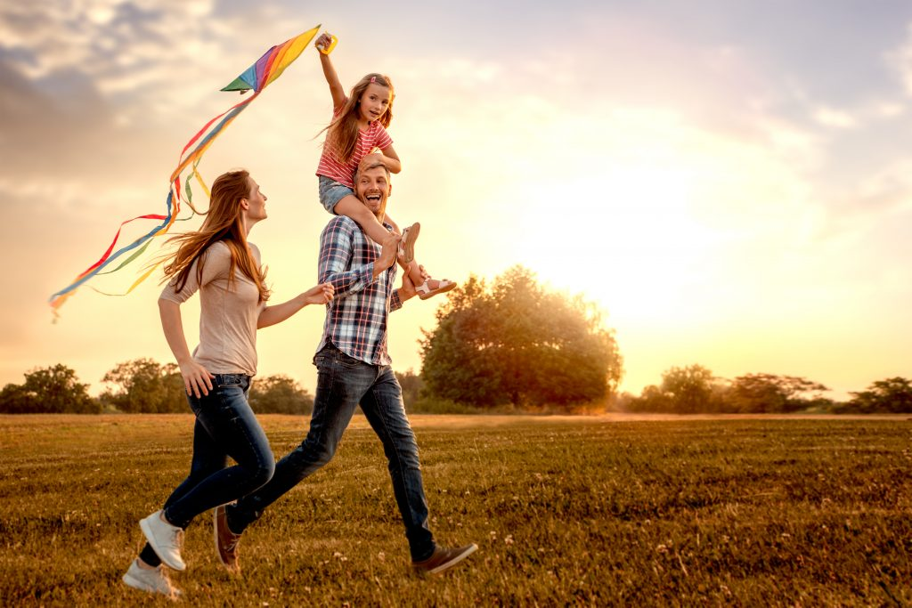 family,running,through,field,letting,kite,fly