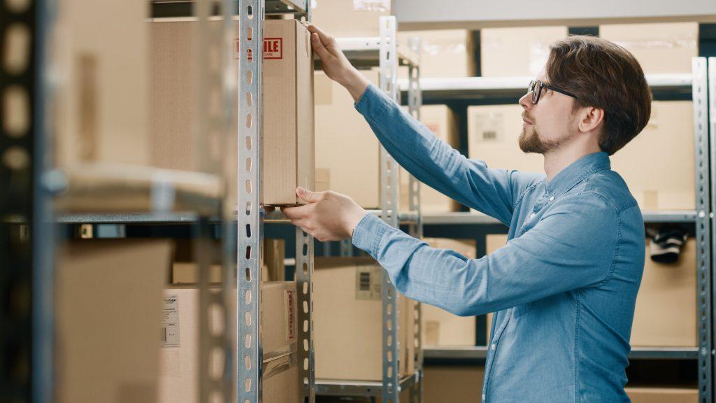 warehouse,worker,puts,cardboard,box,on,a,shelf.,in,the