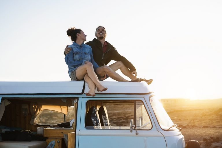 happy,couple,sitting,on,top,of,minivan,roof,at,sunset