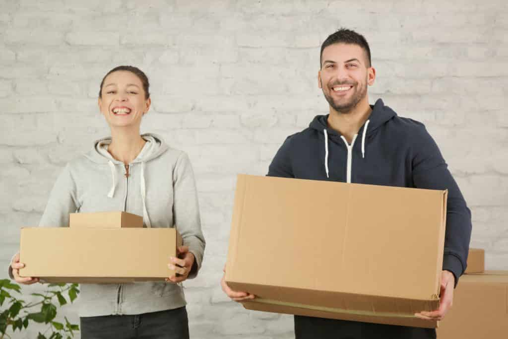 young,happy,couple,holding,cardboard,boxes,,moving,into,the,new
