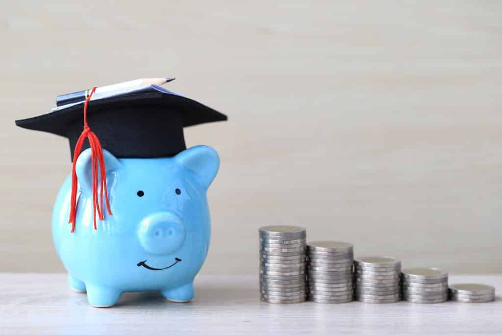 graduation,hat,on,blue,piggy,bank,with,stack,of,coins