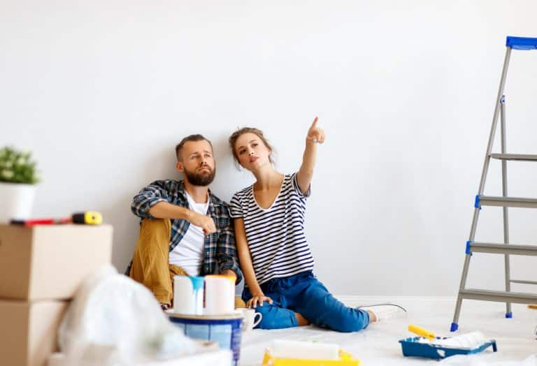 young,couple,woman,pointing,away,for,boyfriend,while,sitting,near
